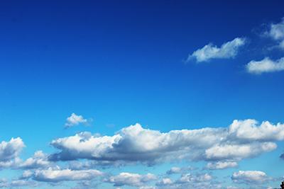 Valkoisia ja vaaleanharmaita pilviä sinisellä taivaalla.