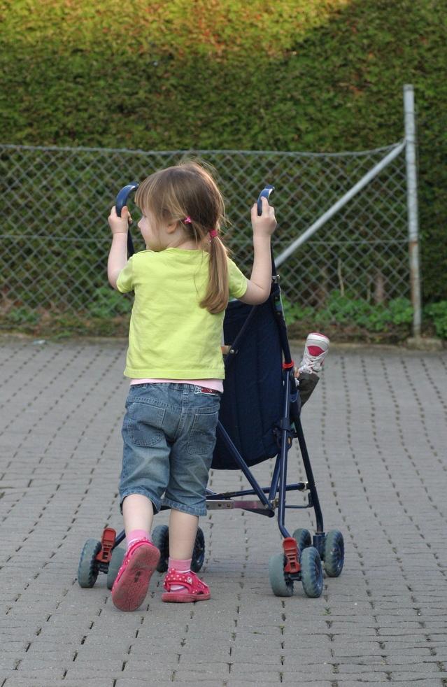 Pieni tyttö työntää vauvaa rattaissa.