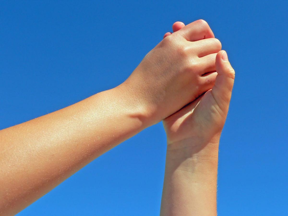 Käsi pitää kiinni toisesta kädestä.