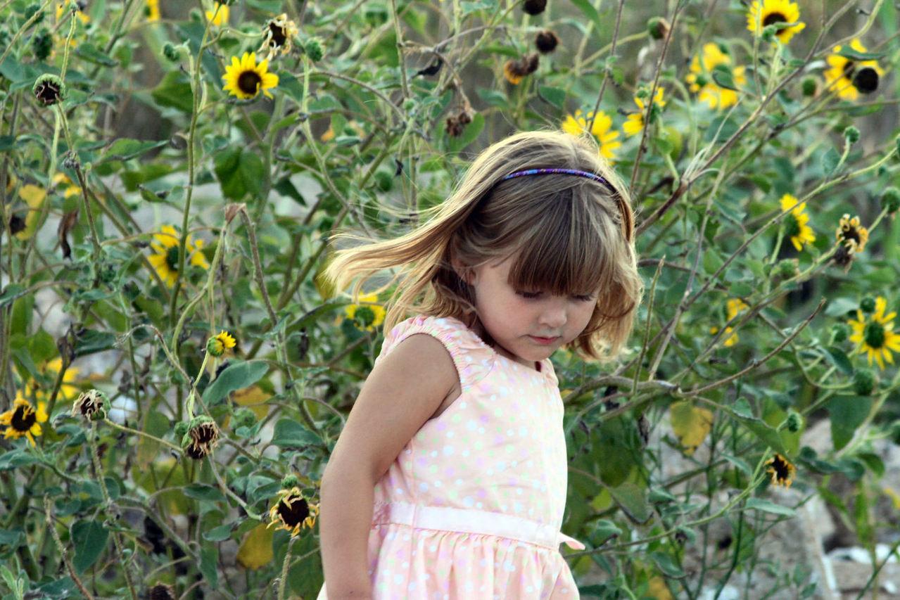 Tyttö auringonkukkapellolla.