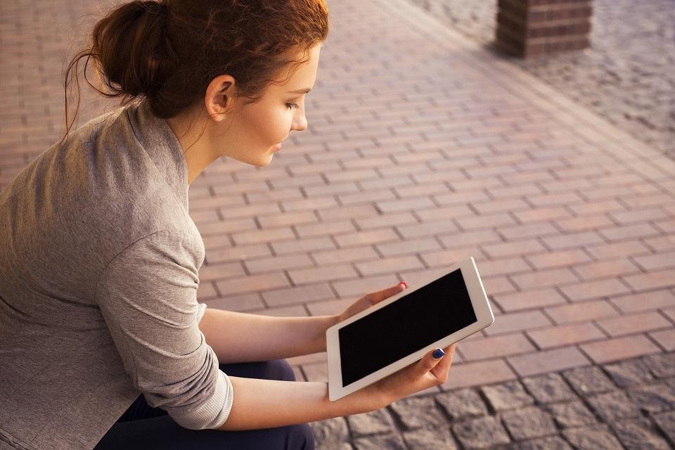 Nainen istuu ja lukee tabletilta.