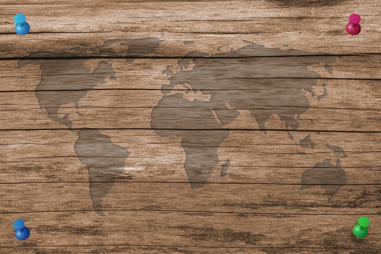 Maailman kartta ja neljä värikästä karttamerkkineulaa kulmissa.