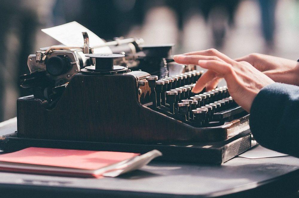 Kirjoituskone ja kirjoittavan henkilön kädet