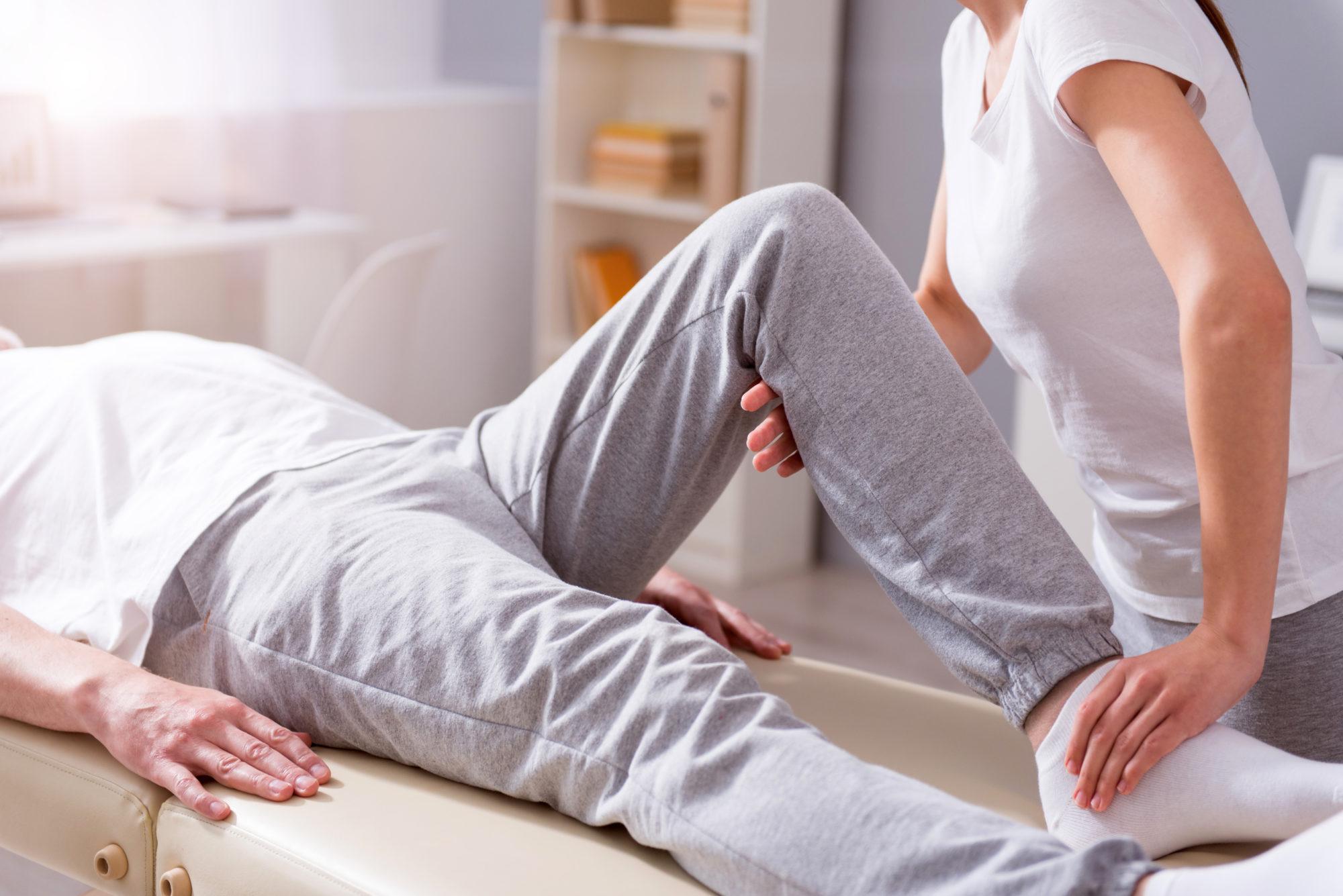 Fysioterapeutti koukistaa makuulla olevan henkilön jalkaa.