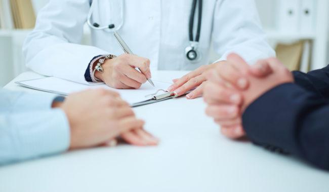 Lääkäri kirjoittaa paperille, kasi muuta ihmistä istuu vieressä.
