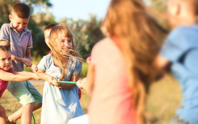 Joukko hymyileviä lapsia leikkimässä.