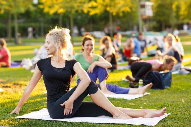 Joukko naisia jumppaamassa puistossa.puistossa