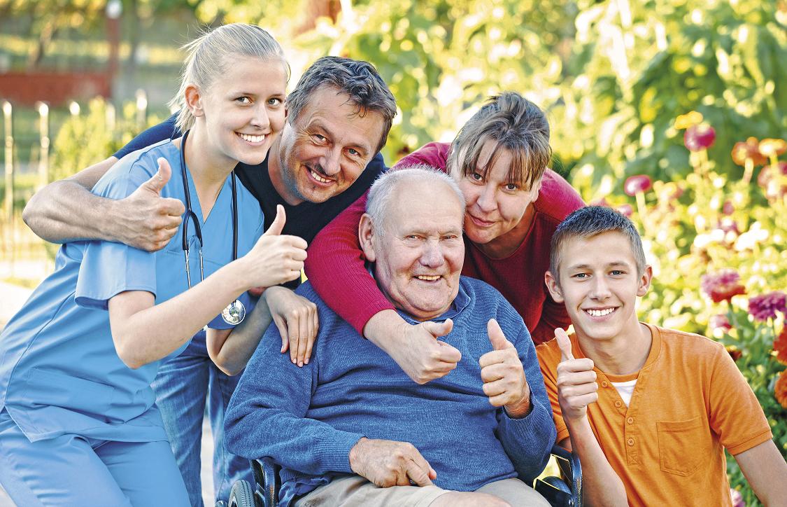Eri-ikäisiä hymyileviä ihmisiä nostamassa peukalot ylös.