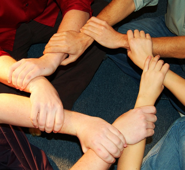 Neljän ihmisen kädet muodostavat ympyrän