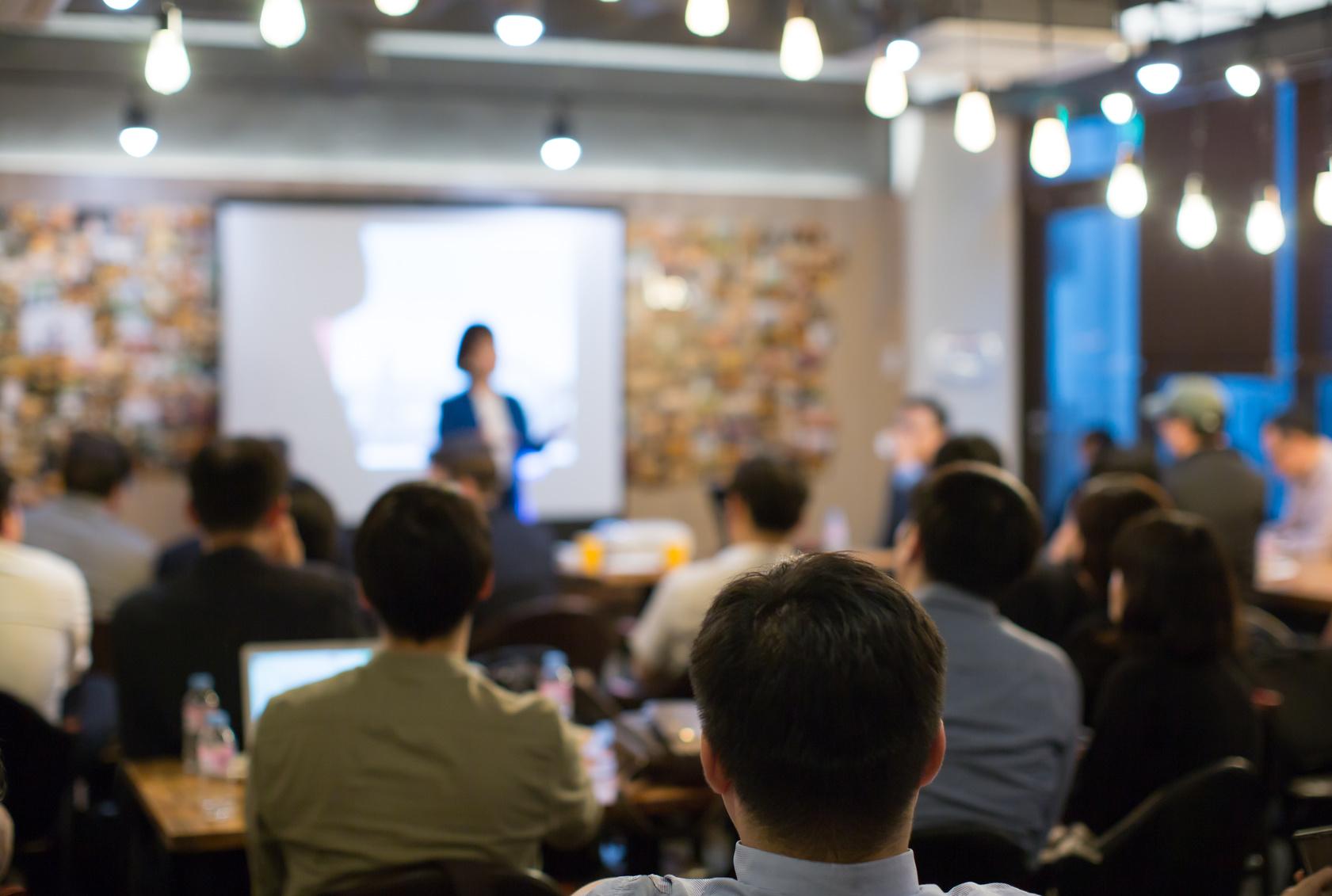 Ihmisiä kokoustilassa kuuntelemassa luennoitsijaa.
