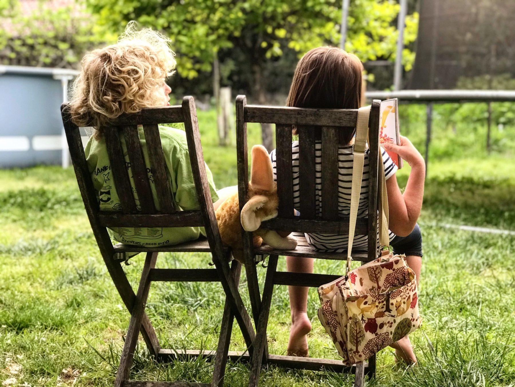 Kaksi lasta istuu puutarhatuoleissa selin kuvaajaan.