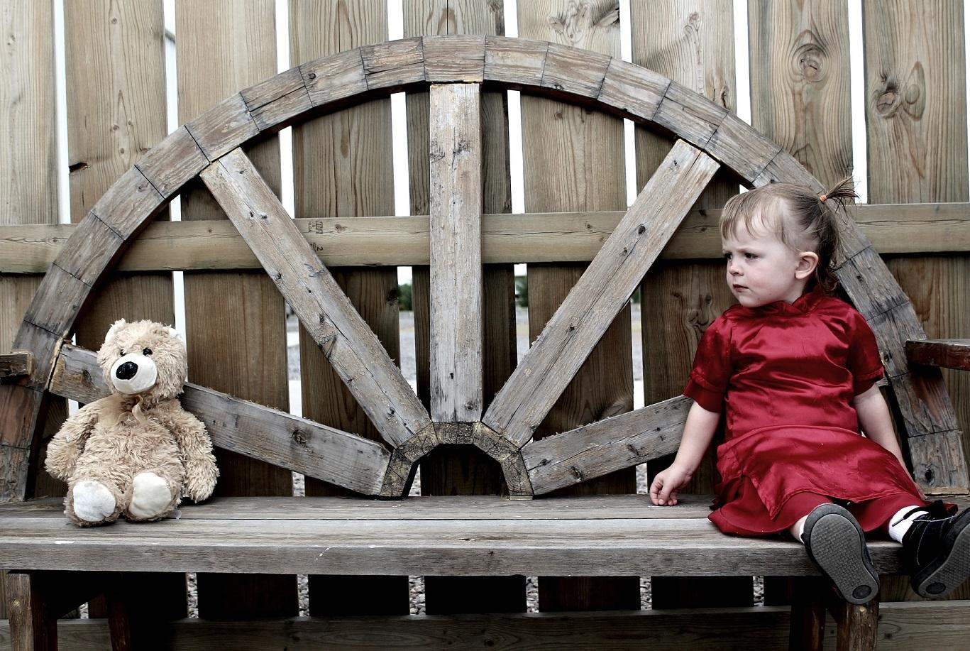 PInei saparopäinen tyttö istuu puisen penkin päässä ja nalle toisessa päässä.