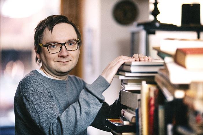 Antti kirjahyllyn vierellä antikvariaatissa.
