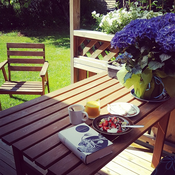 Nurmikolla kesäkalusteet, pöydällä kukkia, kirja ja aamiaiskattaus.