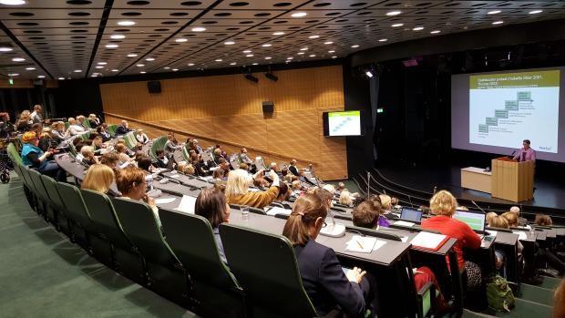 Yleisöä auditoriossa seuraamassa luentoa.