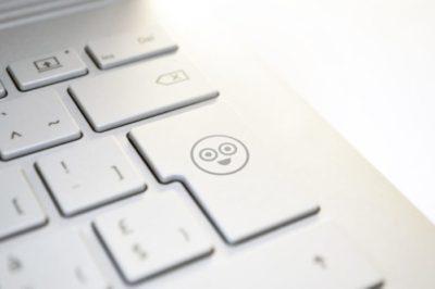 Tietokoneen näppäimistö, jossa on hymynaama-ikoni.