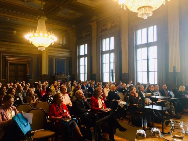 Konferenssiyleisöä istumassa salissa.