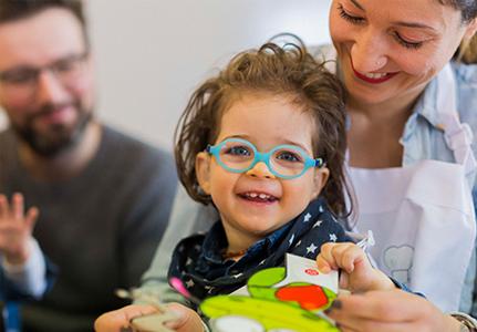 Hymyilevä silmälasipäinen lapsi.