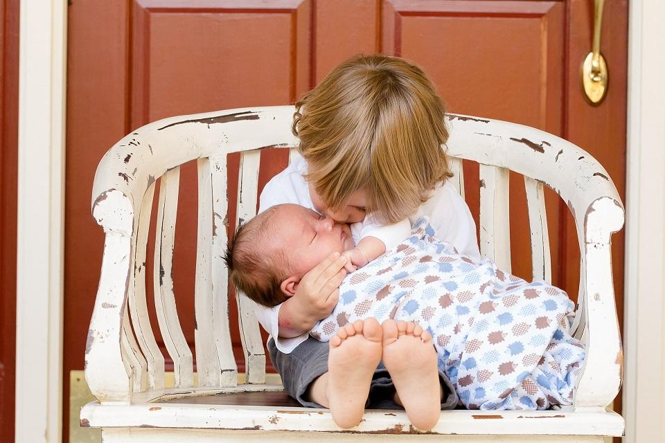 Pieni lapsi istuu penkillä ja pitää vauvaa sylissä
