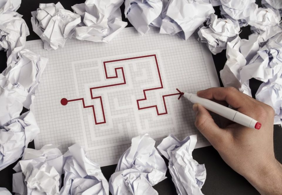 Kädessä oleva kynä piirtää reitin paperille piirretyn labyrintin läpi
