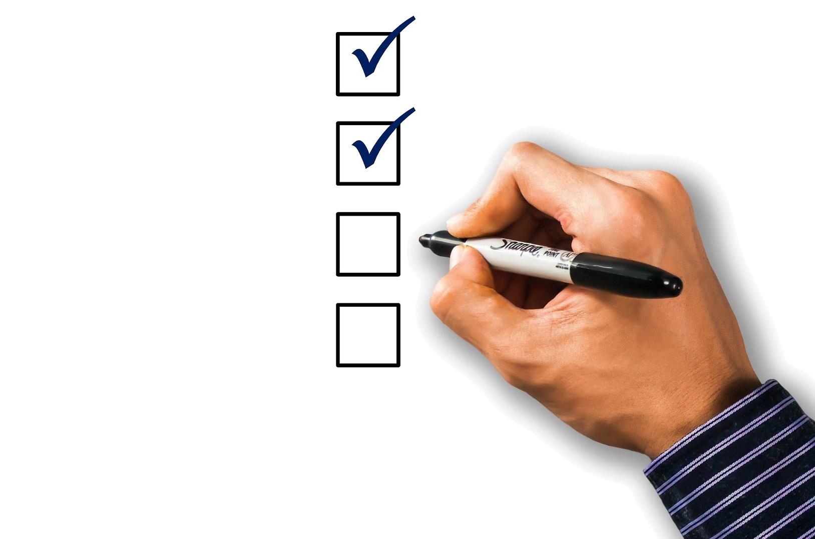 Käsi, joka pitelee kynää ja tarkistuslista.