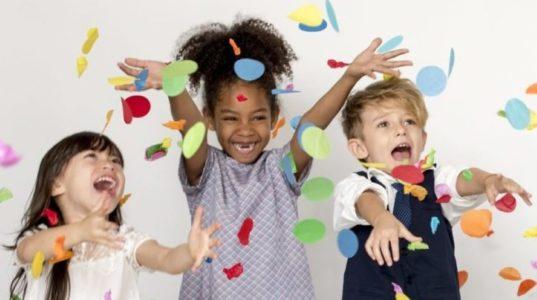 Iloiset lapset heittelevät värikästä konfettia ilmaan