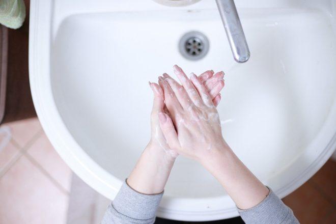 Saippuoidut kädet pesualtaan yllä.