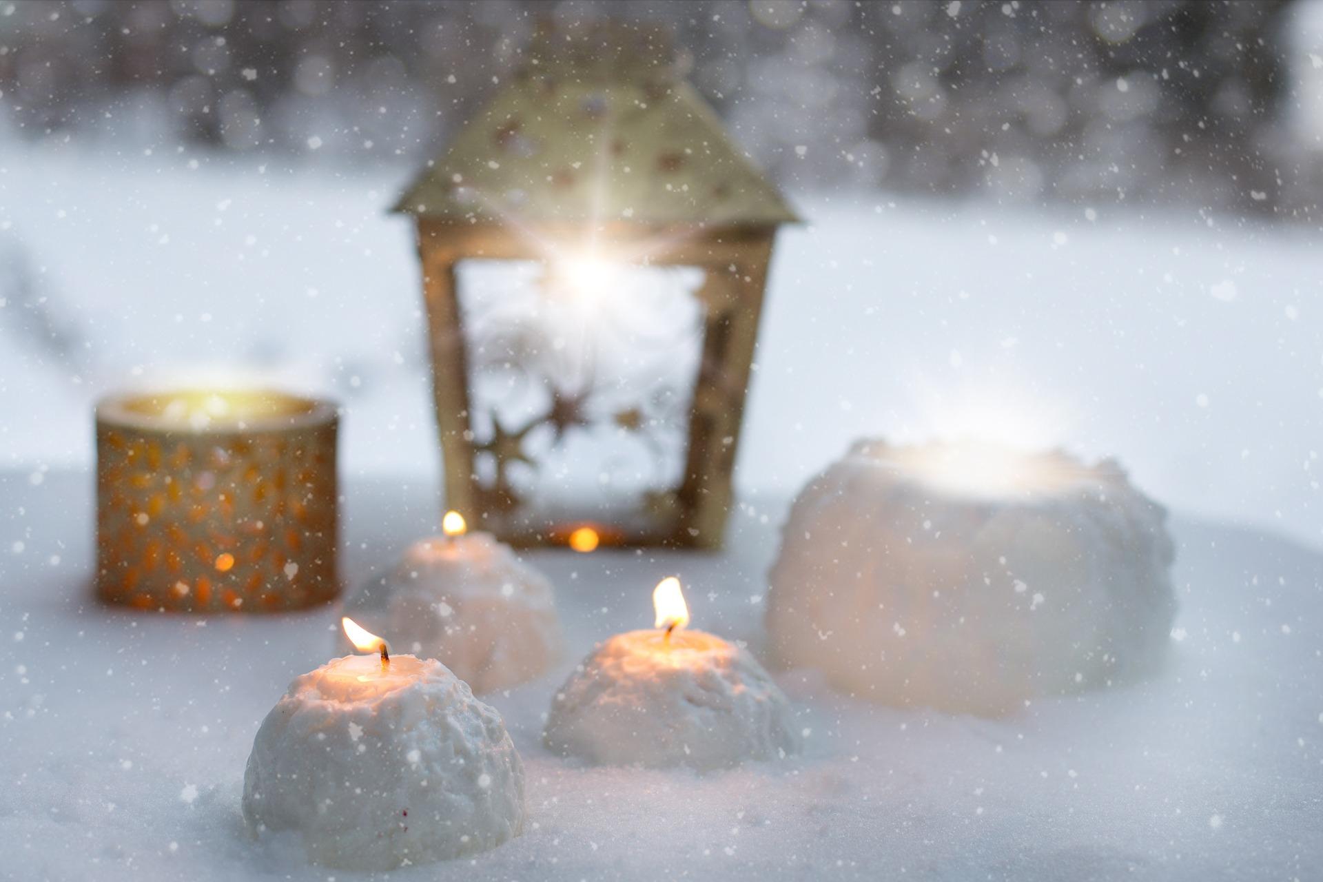 Kynttilöitä ja valoa hohtava lyhty hangella.