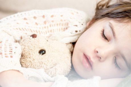Nukkuva lapsi nalle kainalossa
